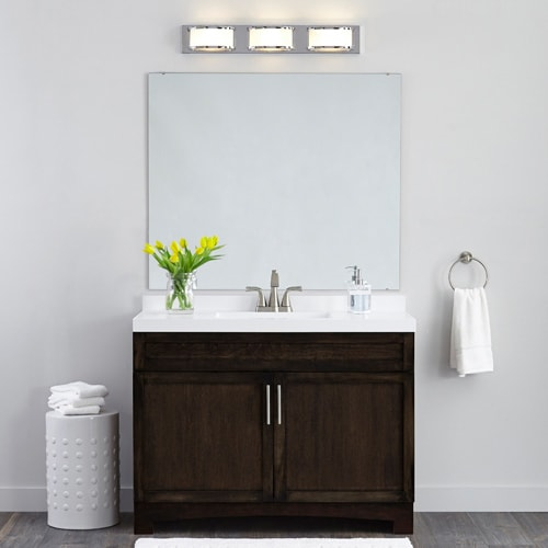 Clean, modern bathroom with dark wood vanity, white walls, white counter and unframed vanity mirror, with a pop of color from yellow tulips.