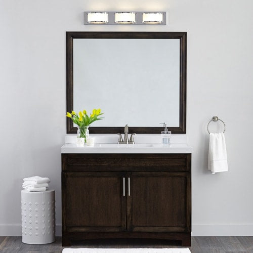 Modern, streamlined bathroom featuring a dark wood vanity, matching dark wood frame in Chelsea Espresso, white countertop and light walls.
