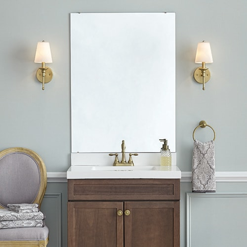 Traditional bathroom vanity and unframed mirror in a green/grey bathroom with gold hardware and lighting.