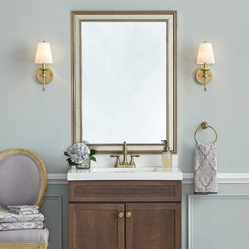 Classic bathroom completed with a mirror frame in Kelso Gold-washed Silver, which compliments the gold  faucet, knobs, and sconces.