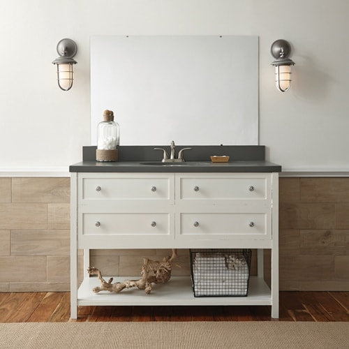 Coastal style bathroom features a white vanity, grey stone counter and nautical lighting.