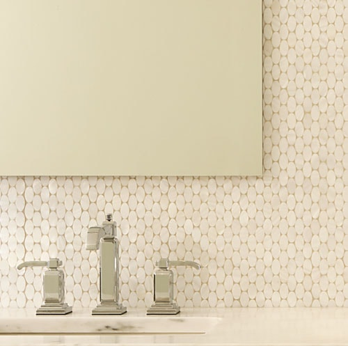 Close up of unframed bathroom mirror on tiled wall and above a marble vanity with silver faucet.
