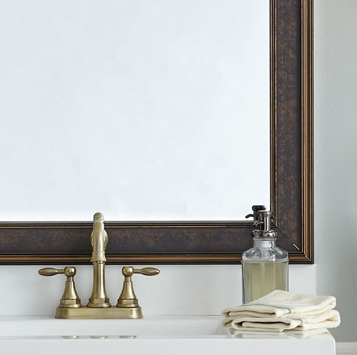 Close up of Kelso Bronzed Brown mirror frame atop a plate glass  mirror and accompanied by a white counter and gold faucet.