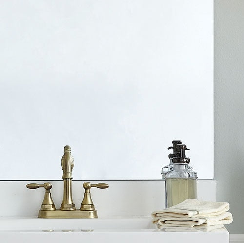 Corner shot of unframed mirror, white counter and gold faucet.