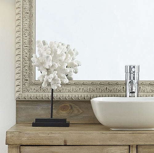 Close up showcasing the intrique detail of the Newport Weathered White mirror frame on a vanity mirror.