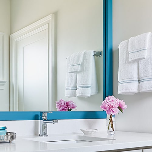 Ocean Aegean Blue mirror frame situated above the vanity.