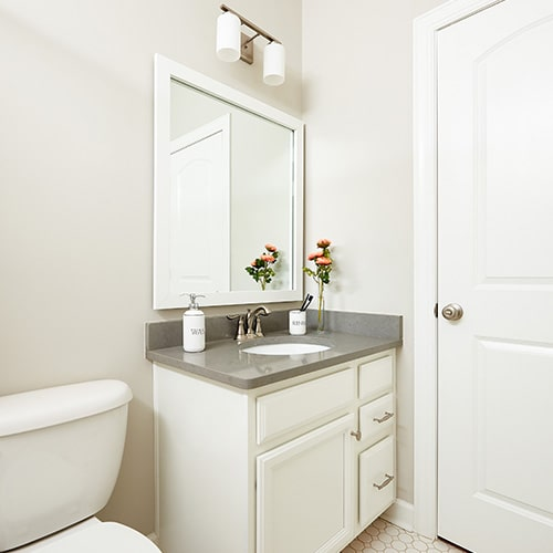 Highline Slim Bright White mirror frame situated above the vanity.