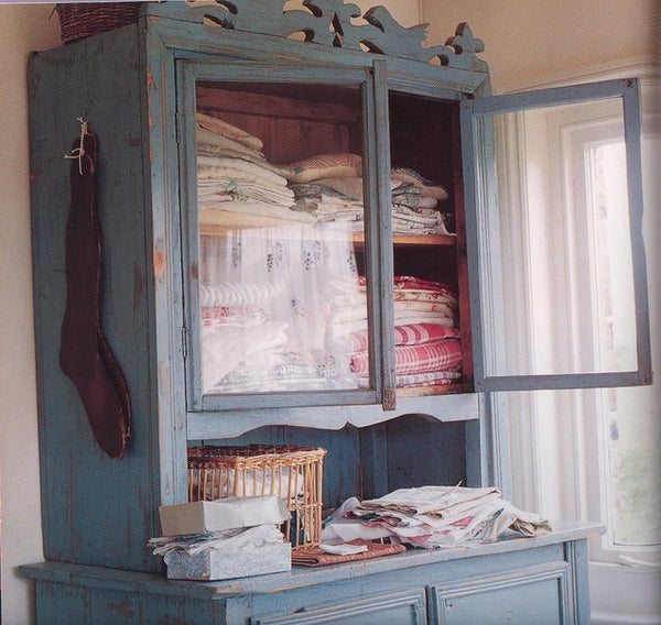 Blue vintage linen closet with linens inside