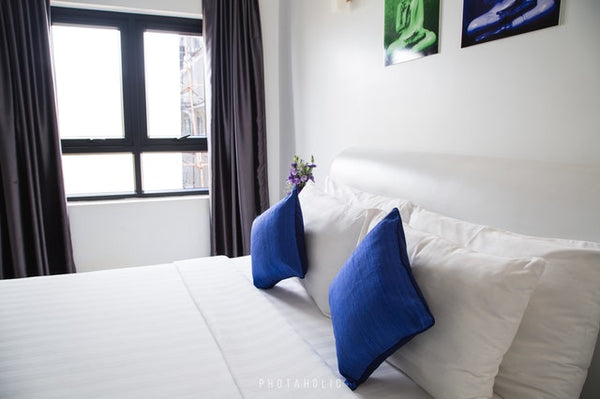 white mattress with blue pillows