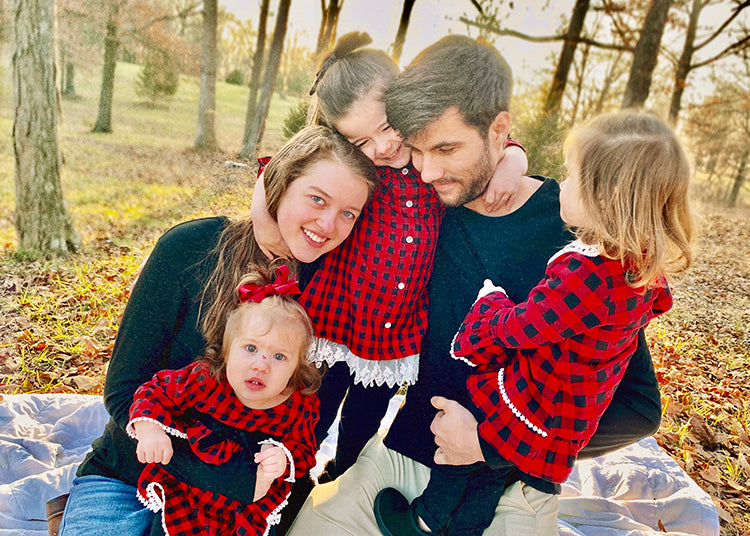 Author, Kaitlin Domangue hugging her family: three daughters and husband
