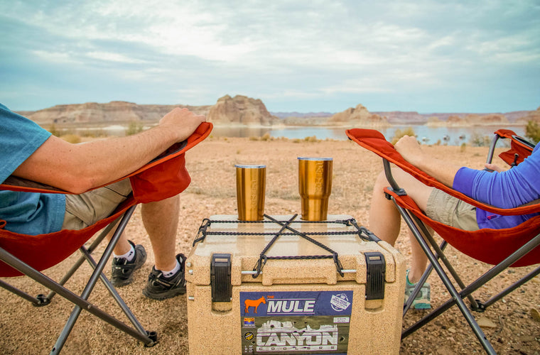 couple sits by cooler at lake