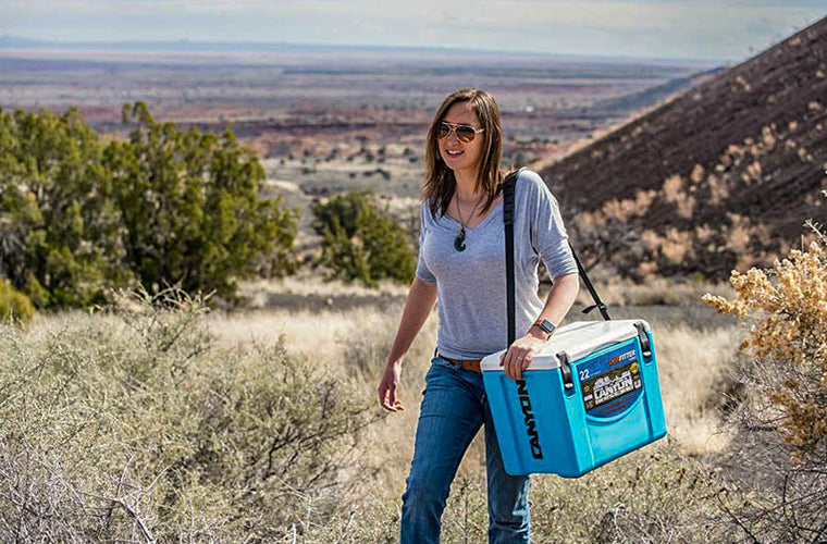 woman carries cooler
