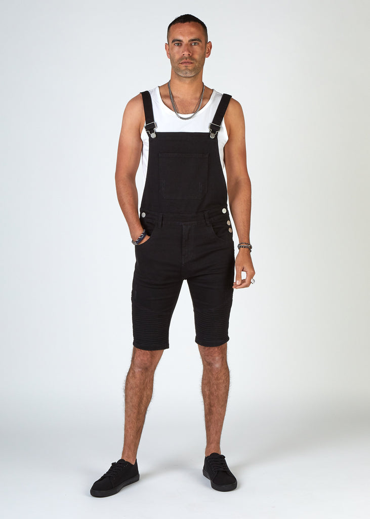 Full front shot with male model wearing Trafford skinny black dungaree shorts, a white vest and black trainers