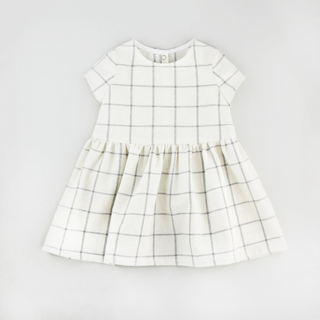 Modern Check Baby Dress Sewing Pattern on a Grey Background