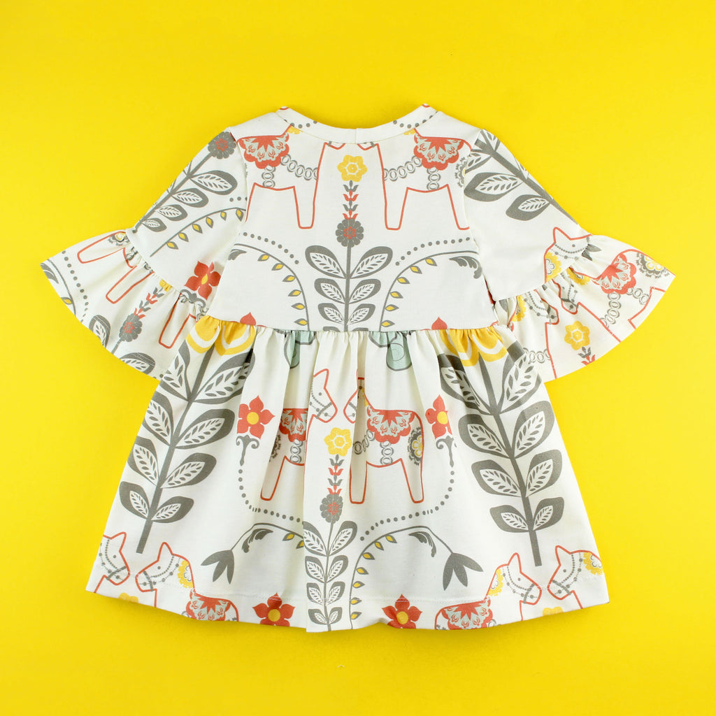 back of Bell Sleeve knit dress in floral dala horse fabric on yellow background