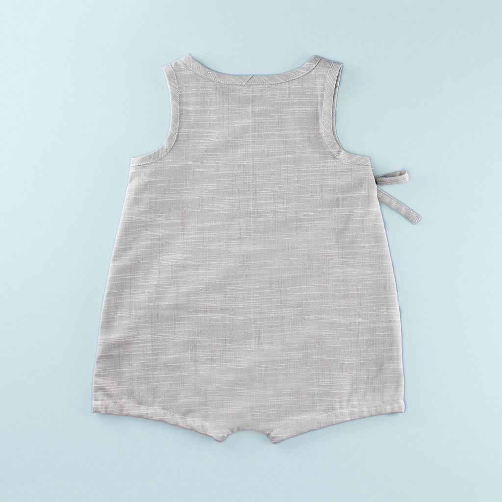 Back of Sleeveless Wrap up Romper on a Light Blue Background