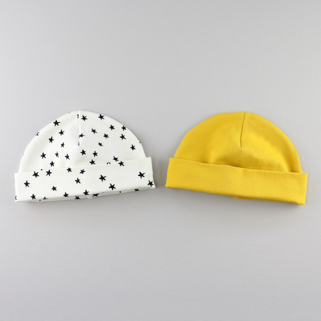 Mustard yellow and star baby hats with the band folded