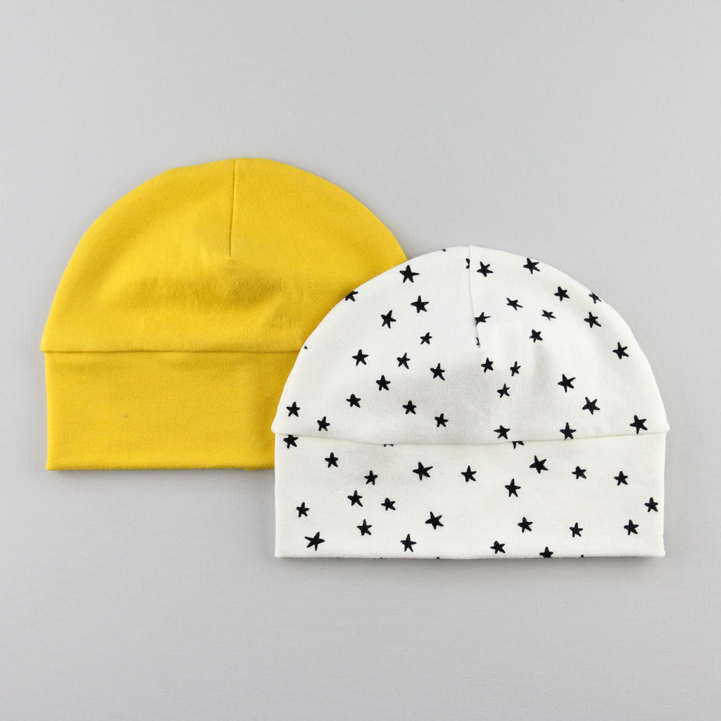 a mustard yellow baby hat behind a white hat with stars