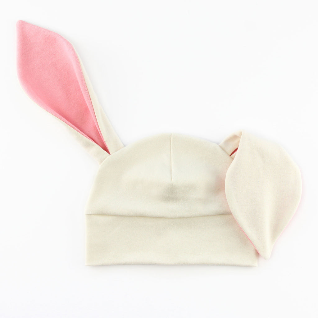 baby hat with bunny ears in white and pink knit fabrics.