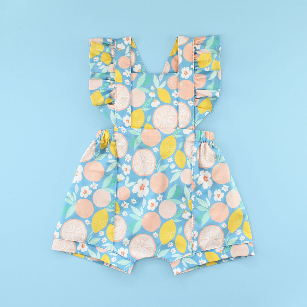 Flutter Sleeve Rainy Day Romper In fruit Fabric on Bright Blue Background