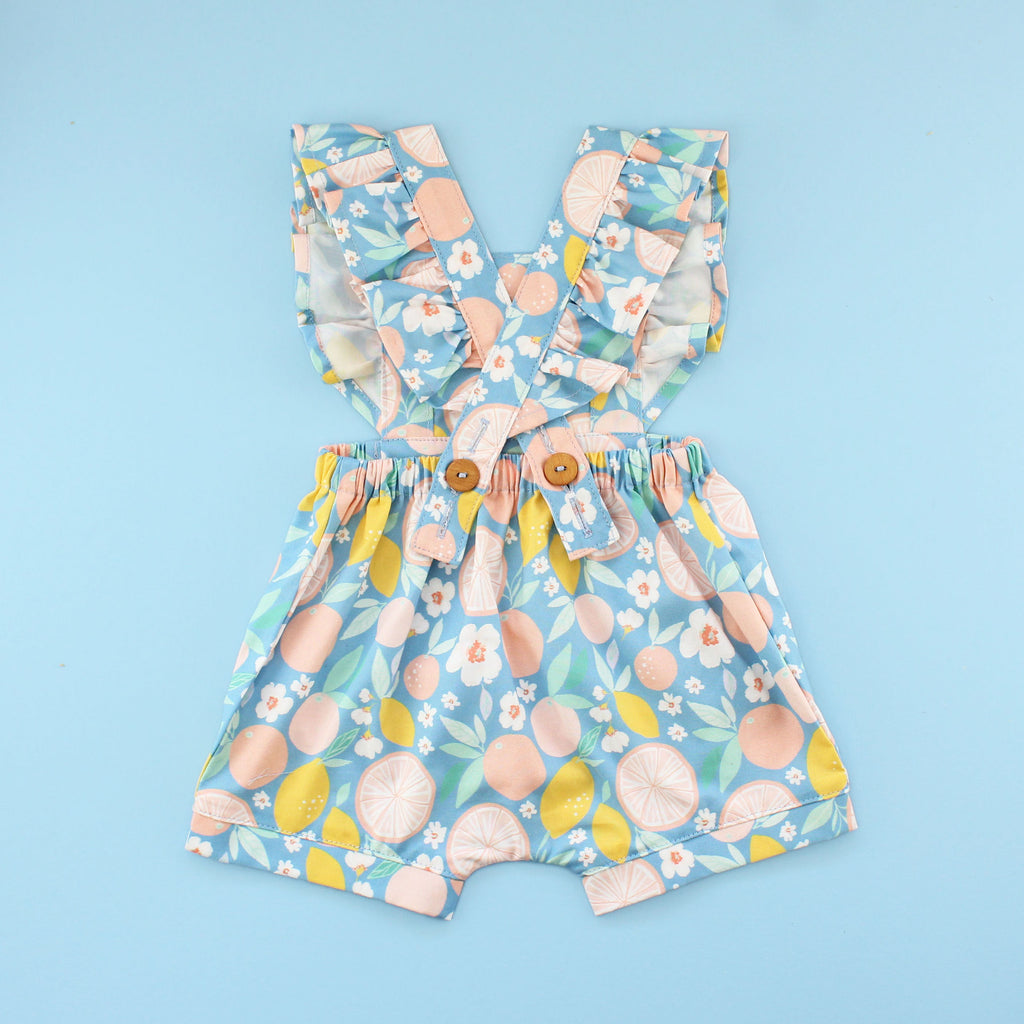 Back of Flutter Sleeve Rainy Day Romper In fruit Fabric on Bright Blue Background