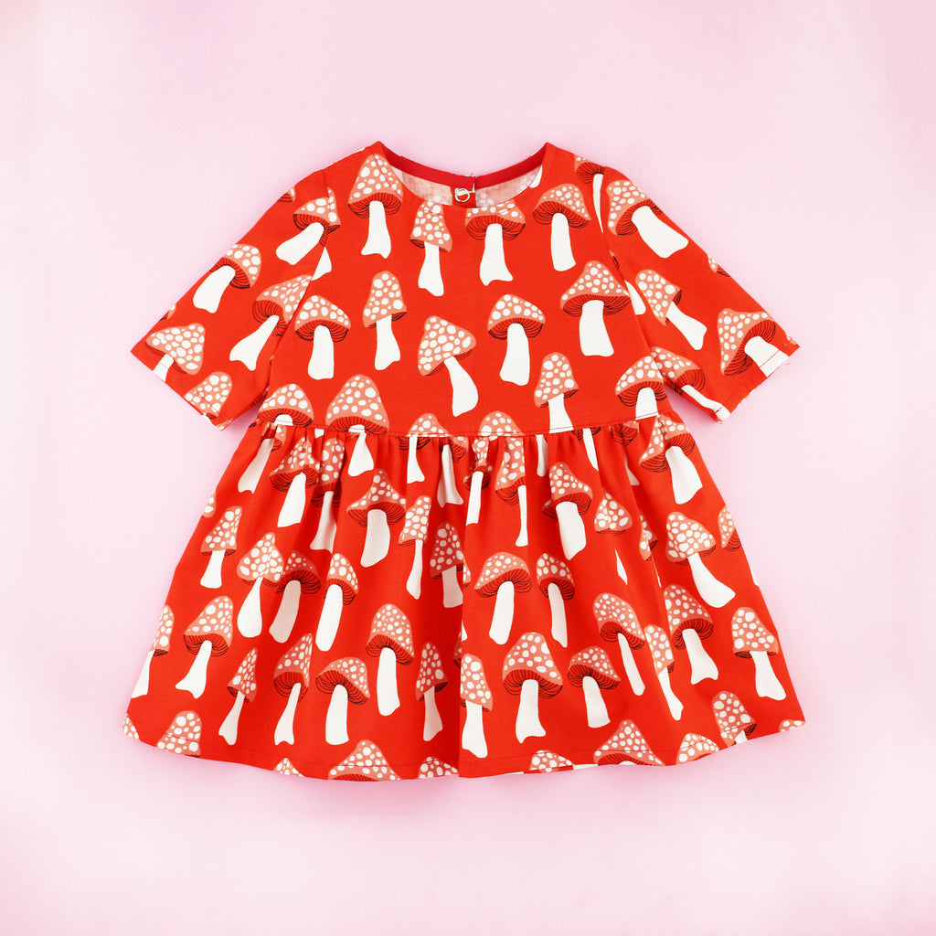 Red Mushroom Print Three Quarter Sleeve Toddler Dress on a Pink Background