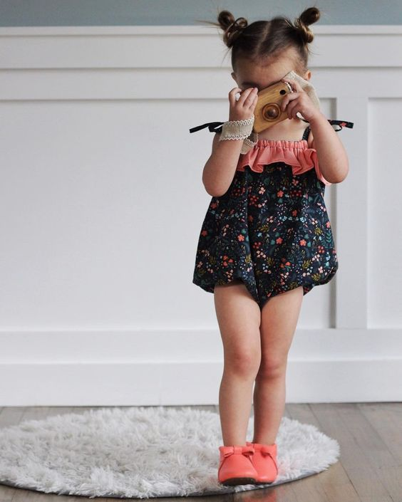 Toddler Girl in Black Floral Tie Strap Romper Holding a Wooden Camera