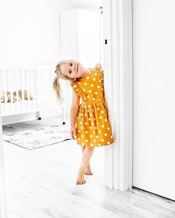 Toddler Girl in Bright Yellow Polka Dot Ruffle Dress Standing in White Room