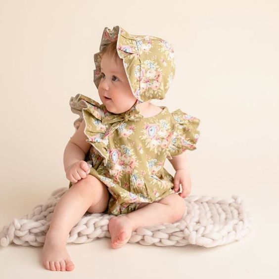 Baby Wearing Mustard Floral Ruffle Romper and Ruffle Bonnet White Sitting on Chunky Knit Blanket