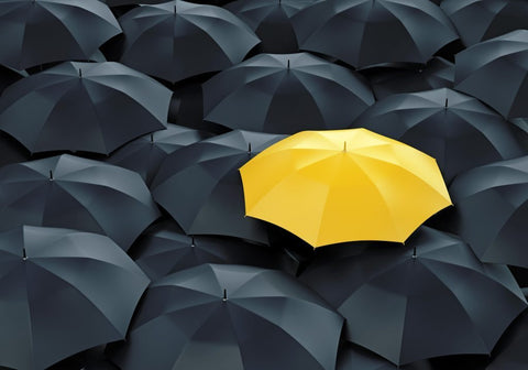 an image of a yellow umbrella surrounded by dark umbrellas