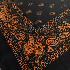 Black bandana with orange floral paisley print close-up view at an angle