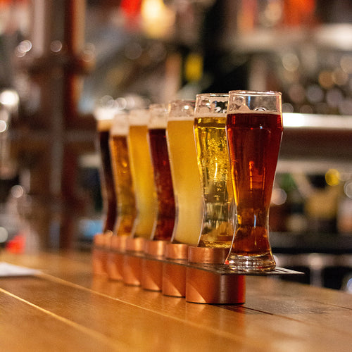 Different types of beer are lined up on a wooden bar.