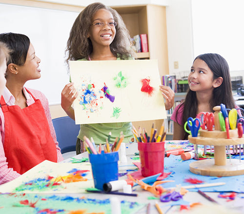 a girl shows her classmates the artwork she created. there is a table infront of her messy with art supplies, glue, feathers, scissors