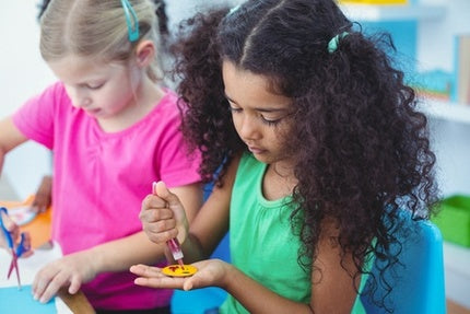 two young girls are in a classroom setting creating art projects