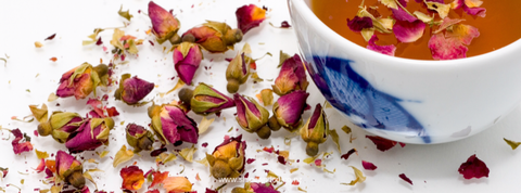 Pot of herbal tea with herbal tea leaves scattered - a beautiful selfcare ritual