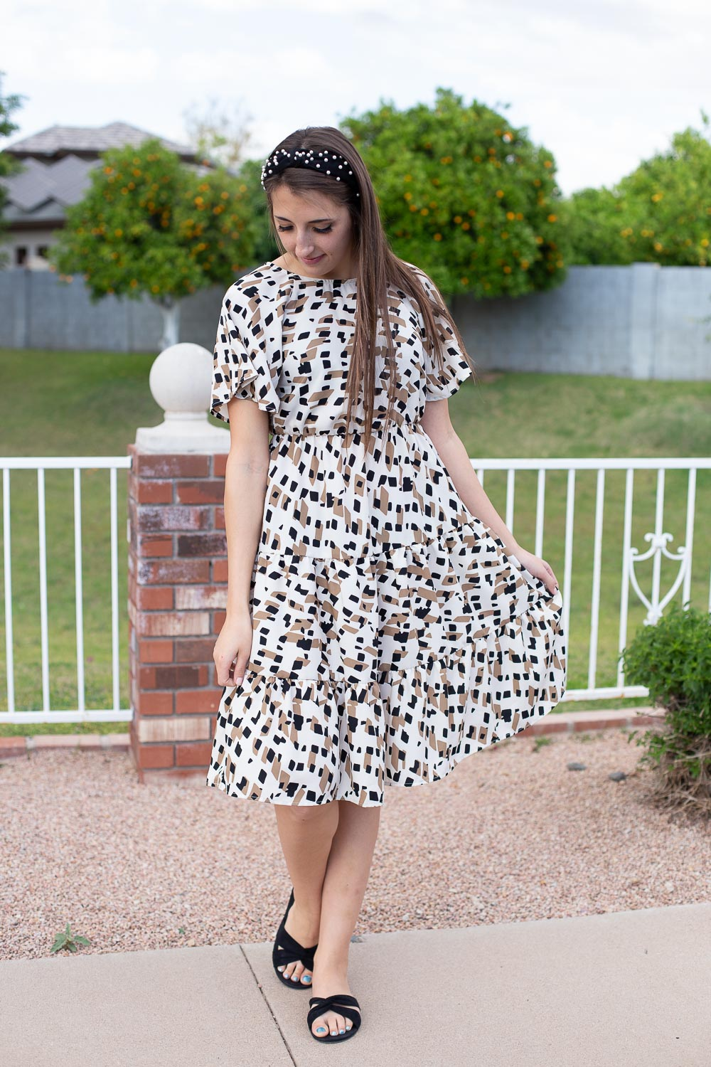 Ivory, brown and black printed dress on model