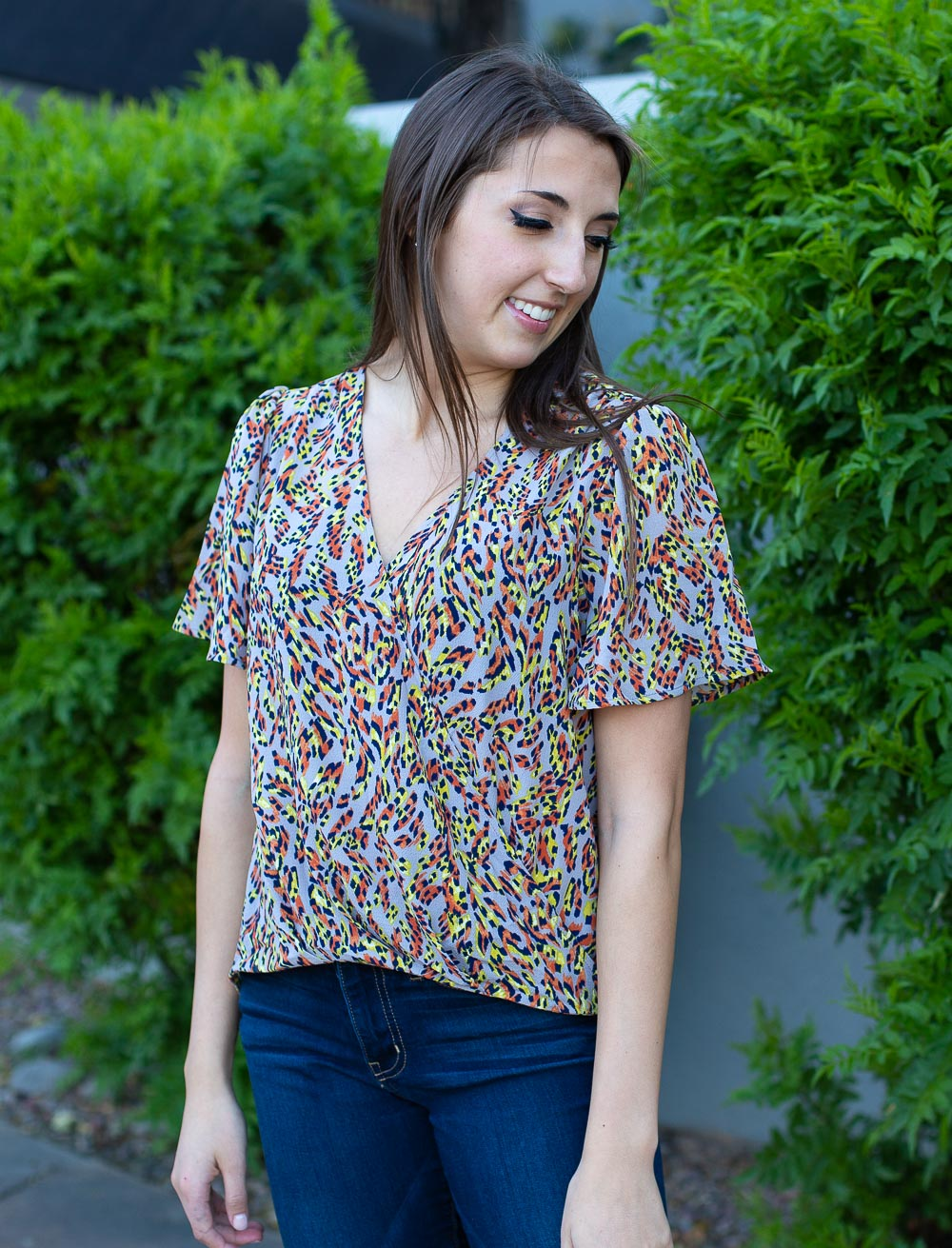 Cross front wrap top with high-low hemline, flutter sleeves and colorful abstract print