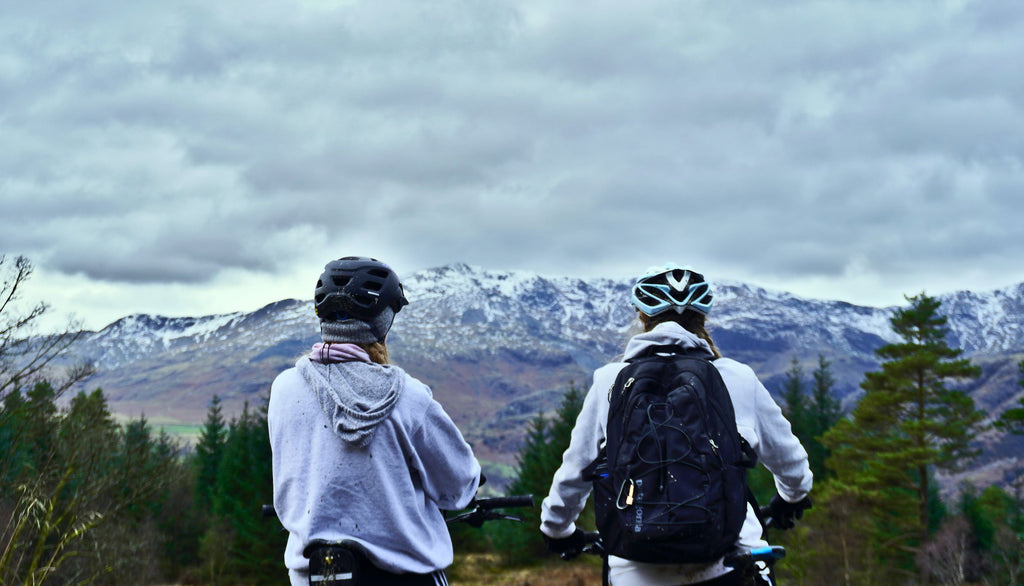 Two mountain bikers look out over a bluff with snow covered mountains in the background