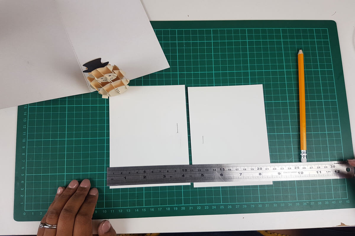 How To Make a 3D Christmas Pop Up Card - picture of cutting slits into the inner cover where you will slide in the pop up snowman