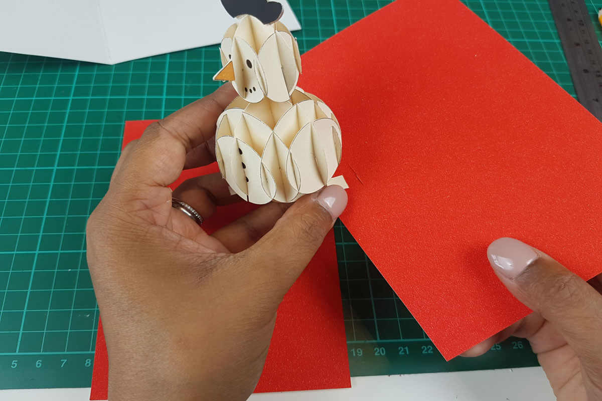 How To Make a 3D Christmas Pop Up Card - picture of slotting the 3D snowman through the cut out slots in the inner cover