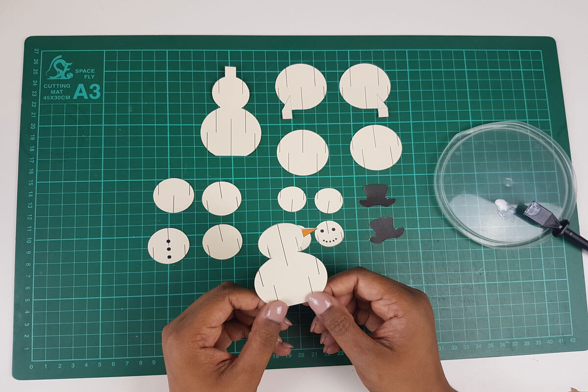 How To Make a 3D Christmas Pop Up Card - picture of gluing the nose onto the snowman