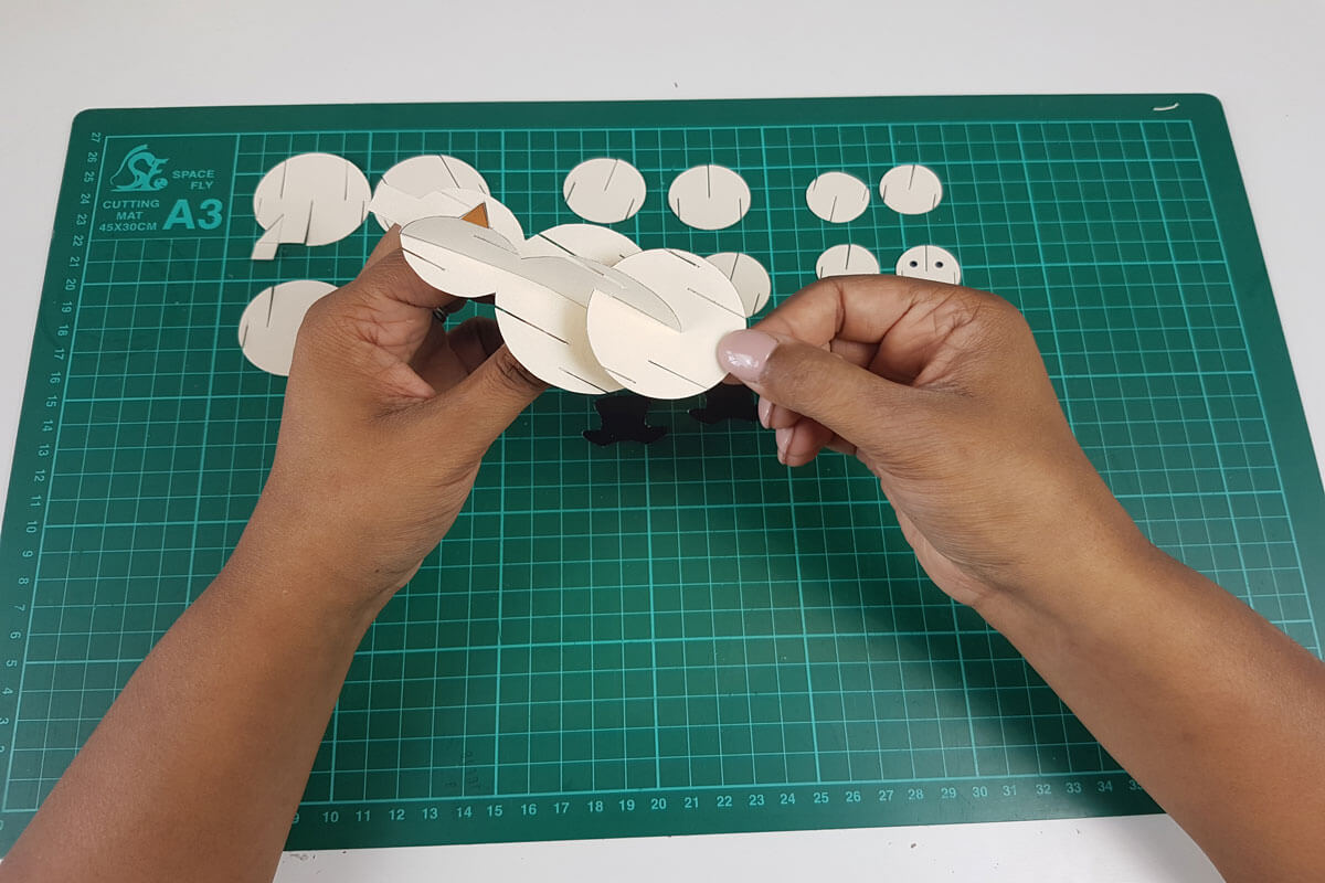 How To Make a 3D Christmas Pop Up Card - picture of slotting the next size of circles to the snowman body