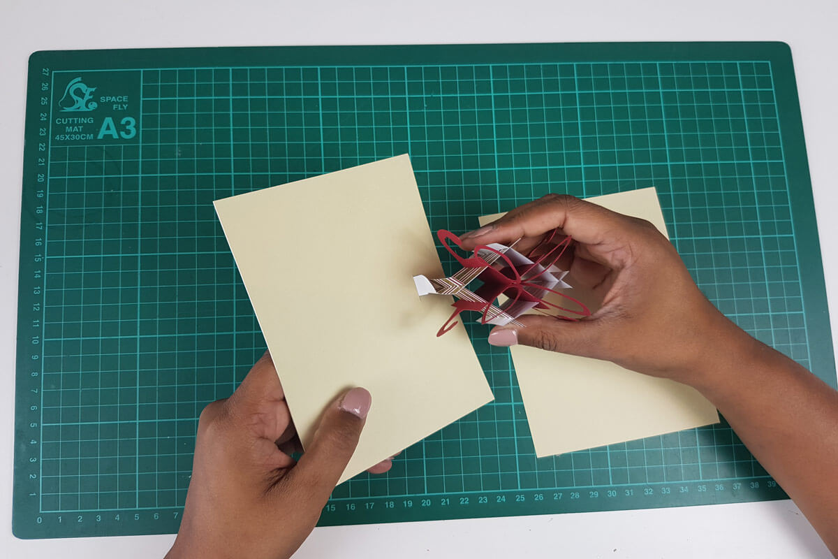 How To Make A Christmas Pop Up Card Tutorial - picture of slotting the tabs on the pop up present through the slits cut in the inner cover