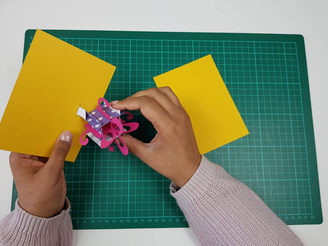 How to make a birthday card pop up card tutorial - picture of slotting the pop up birthday present through the slots