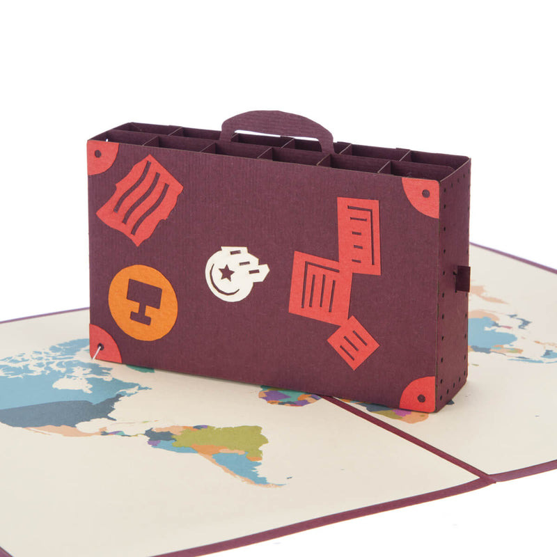 Close up image of bon voyage pop up card featuring a 3D suitcase sitting on top of a world map