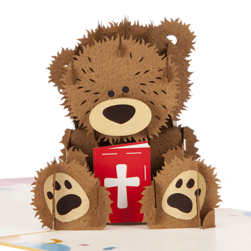 Close up image of Christening Bear Pop Up Card featuring a fluffy brown teddy bear holding a red bible with a cross on the cover