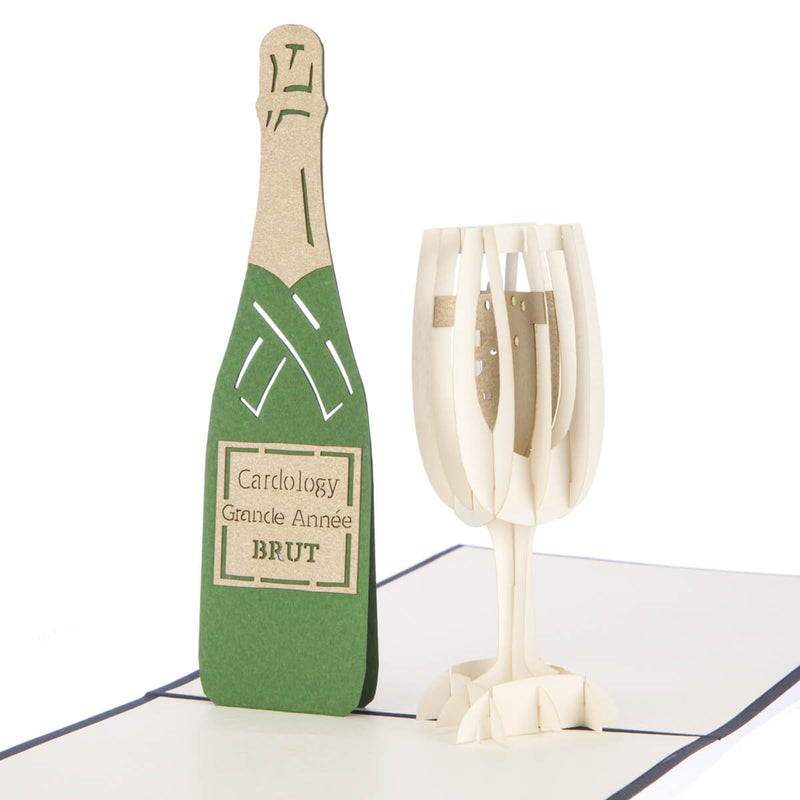 close up of congratulations card featuring a 3D champagne flute filled with bubbly and a green champagne bottle