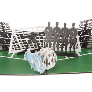 close up image of football pop up birthday card featuring a 3D football and boot taking a penalty with a line of 2D defenders and a goalkeeper