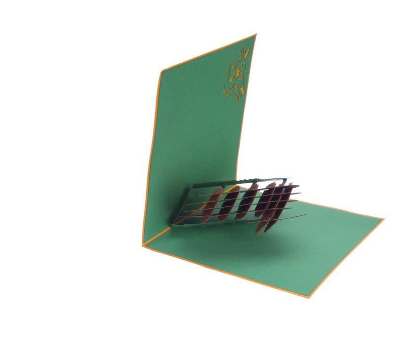 Highland Cow Pop Up Card featuring a 3D bronze highland cow standing among green grass, half open at 90 degrees