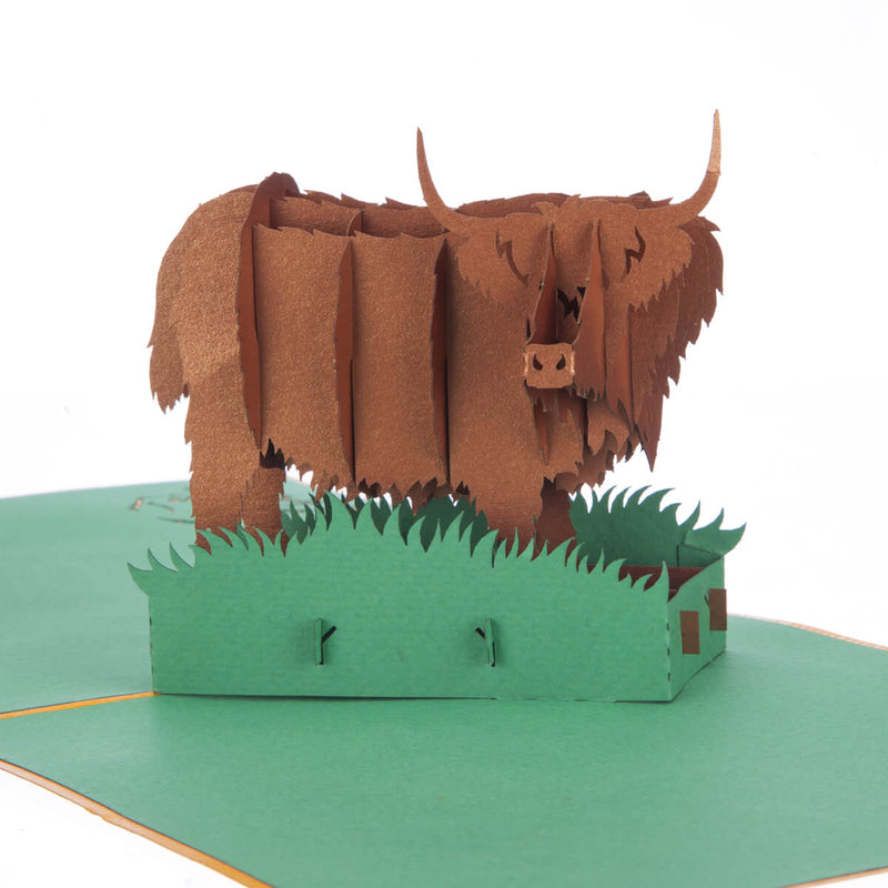 close up image of Highland Cow Pop Up Card featuring a 3D bronze highland cow standing among green grass